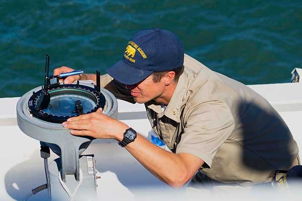 Photo of intern using compass aboard ship