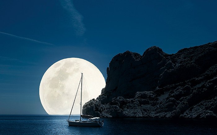 Sailboat Moored at Night with Big Full Moon in Background