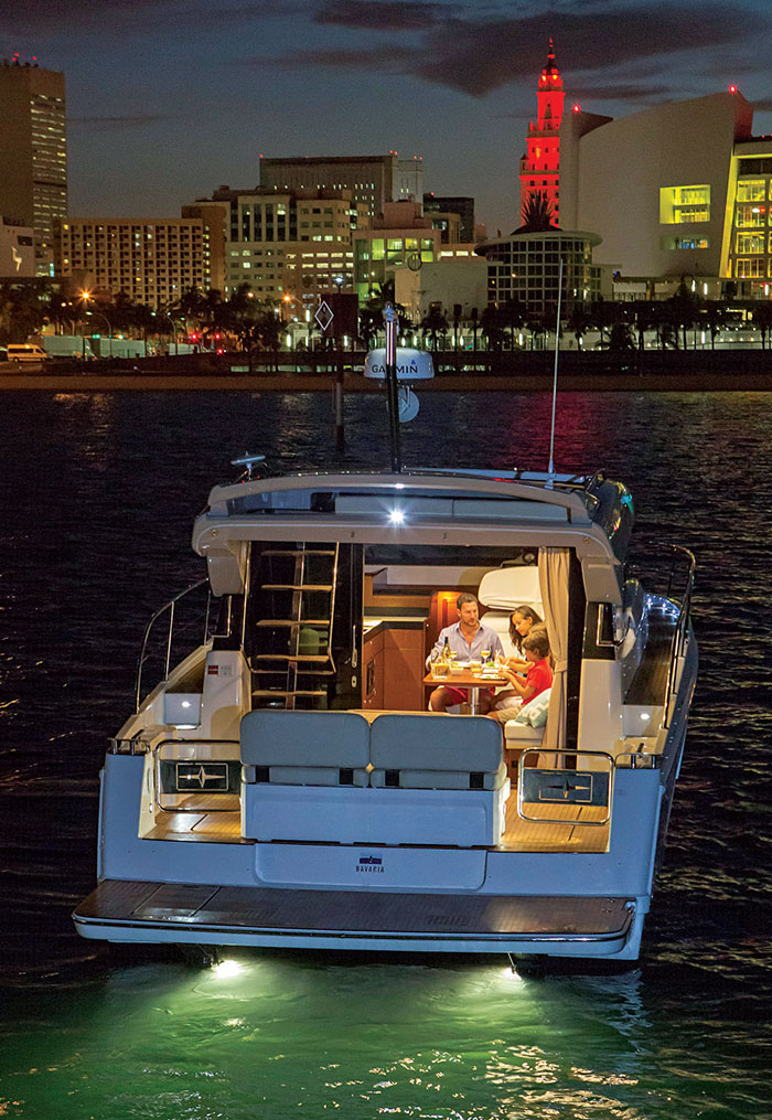 Photo from behind boat at night with a family eating dinner inside the boat and a city in the background