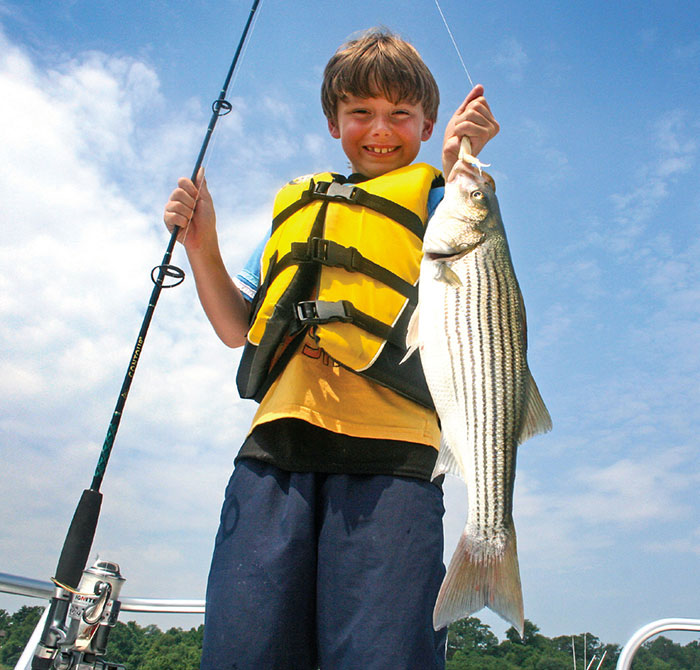Boy in yellow life jacket holding fishing rod and fish