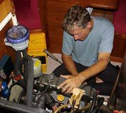 Photo of Douglas changing the oil and replacing a hose on the engine