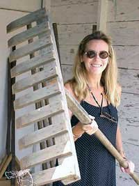 Photo of Bernadette, with a rake used to spread the loose coffee beans
