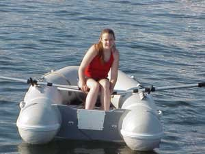 Photo of Kelli rowing an inflatable boat