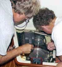 Photo of Harold and Douglas studying and tracing the parts of Ithaka's refrigeration system