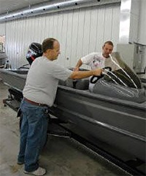 Photo of two men inspecting an aluminum boat