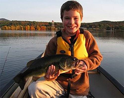 Young fisherman Caleb Reynolds holds up his catch