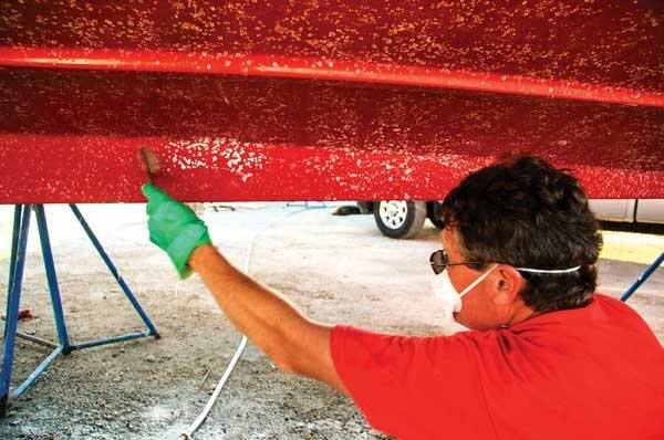 Photo of a man cleaning a boat hull