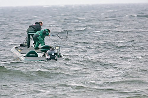 Photo of two anglers fishing in rough water