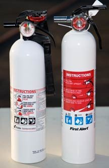 2 white fire extinguishers sit side by side.