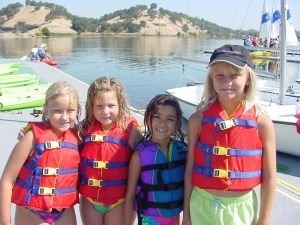 4 girls in lifejackets participate in a junior sailing program.