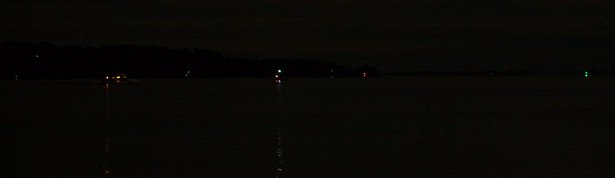 A panoramic view of navigation lights on the water in the pitch black of night.