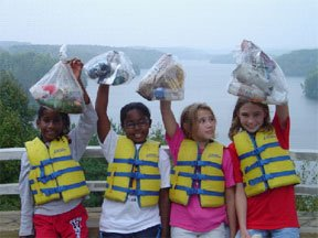 Four children show off the bags of trash they have filled.