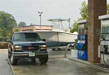 A GMC pickup pulling a center console pulls up to an automotive fuel pump