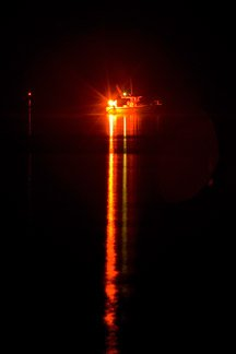 A handheld flare is seen at night on the stern of a boat.