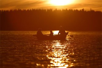 3 people row a boat in a lake at sunset.