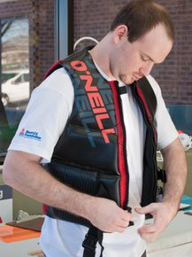 A tester zips the front of his watersport type III lifejacket.