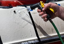 A close-up of a hose rinsing a boat hull.