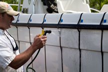 A tester rinses a test are on the boat.