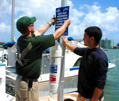 "Two boys install a sign which reads, ""Keep our waterways tangle-free: Recycle your fishing line responsibly."""