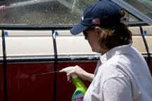A lady sprays cleaner onto the hull of the red powerboat.