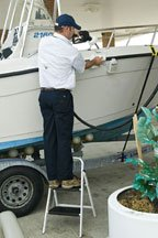 A person fuels their 21 foot center console on the trialer using a special, 'no spill' fuel vent overflow device.