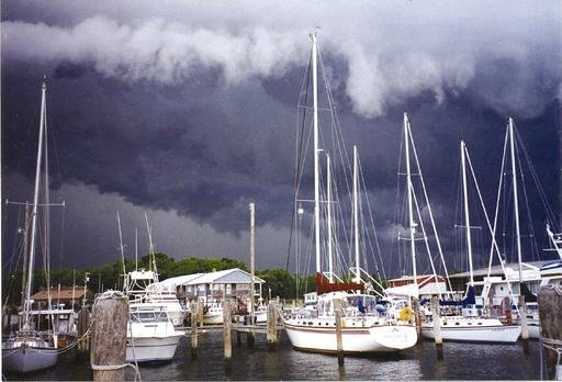 A marina with many boats is shadowed by large storm clouds.