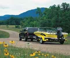 A black truck trailers a yellow ski boat equipped with a outboard