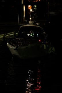 A Sea Ray sits at rest tied to the dock with navigation lights still lit.