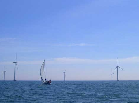 Photo of windmills and a sailboat at sea