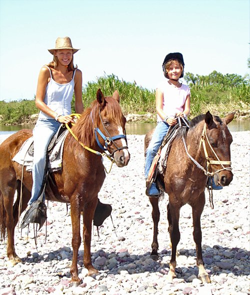 Photo of Olivia and her mom riding horses