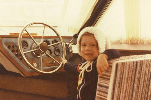 Photo of Stephanie, age 4, at the wheel of her grandfathers 26-foot Penn Yan
