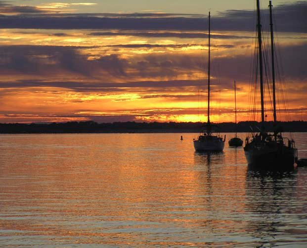 Photo of sunset on the water and boat silhouettes