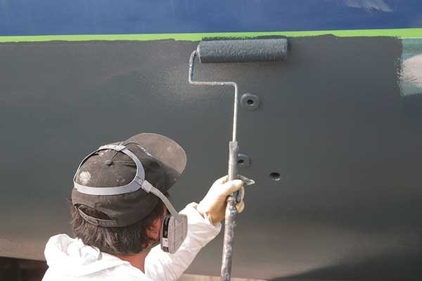 Photo of painting the bottom of a boat with copper paint