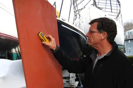 Photo of surveyor inspecting the keel of a boat