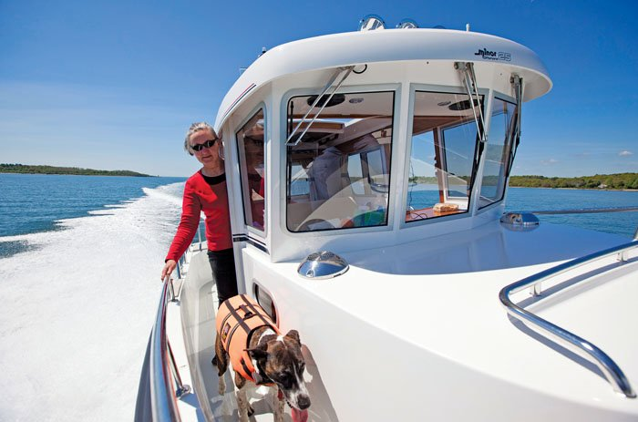 Photo of Joyce Black and her dog aboard her pilothouse cruiser