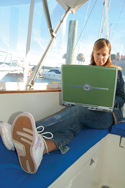 Photo of a woman on a laptop computer aboard a boat