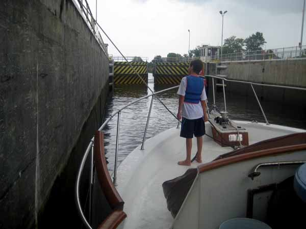 Photo of Nickolas standing on the bow of the Lady Enna while going through the locks