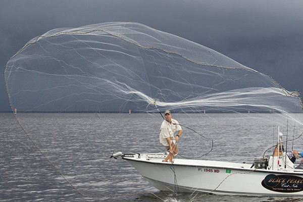 Photo of a fisherman casting his net