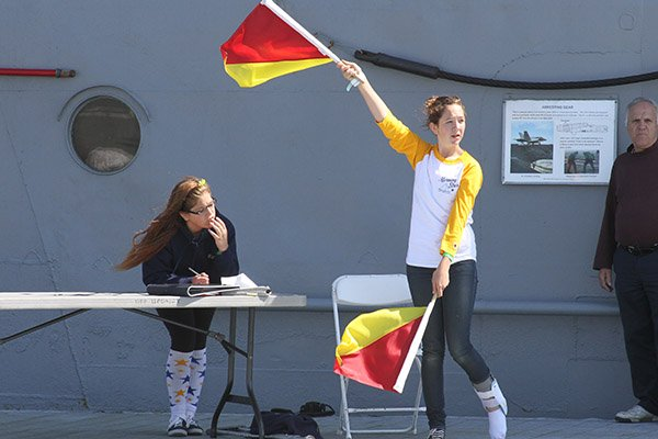 Photo of female using signal flags on a ship