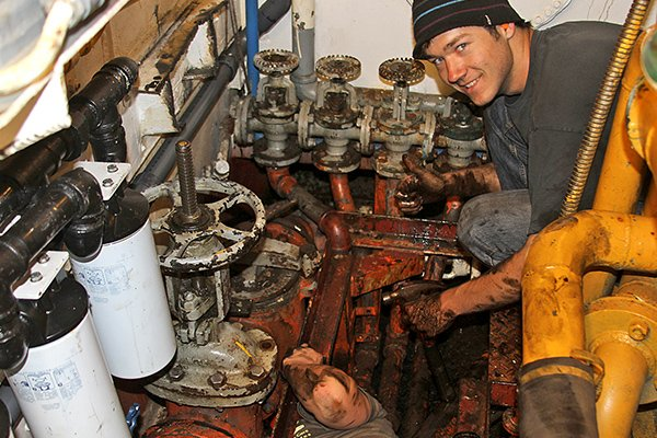 Photo of a Sea Scout working on a boat engine