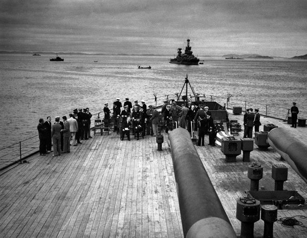 Photo of the big guns of the HMS Prince of Wales, overlooking a gathering of senior British and American staff