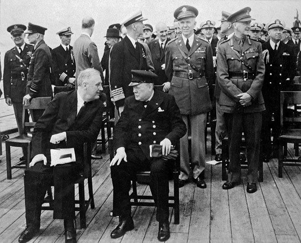 Photo of President Roosevelt and Prime Minister Churchill chat on the deck of HMS Prince of Wales