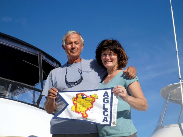 Photo of Bob White and Cathryn Rice display a white burgee, signifying that their Great Loop journey