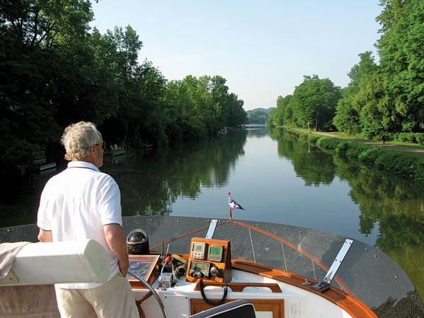 Photo of Tom Blanchard guiding the Stasia Louise across mirrorlike Erie Canal waters