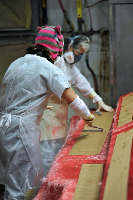 Photo of workers adding sound-absorbing fabric to the hull lay-up