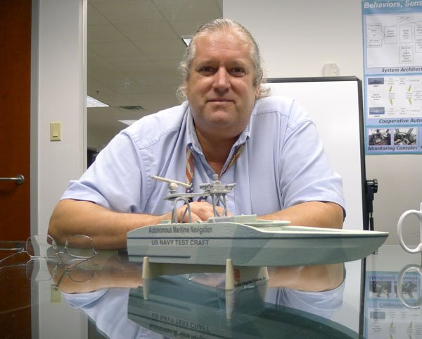 Photo of Robotics expert Eric Hansen and a model of one of his robot boats