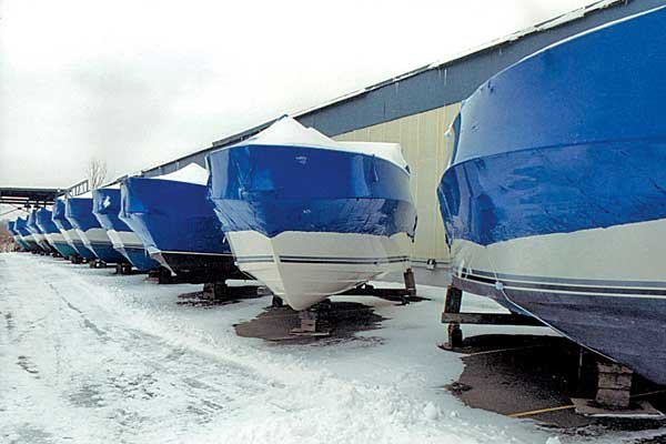 Photo of a row of covered boats stored onshore