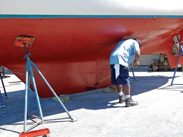 Photo of a man degreasing the bottom of a boat