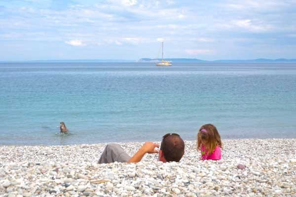 Photo of the author Kevin Walters and his daughter skipping stones into Lake Michigan