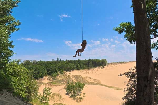 Photo of author's daughter swing high over a dune